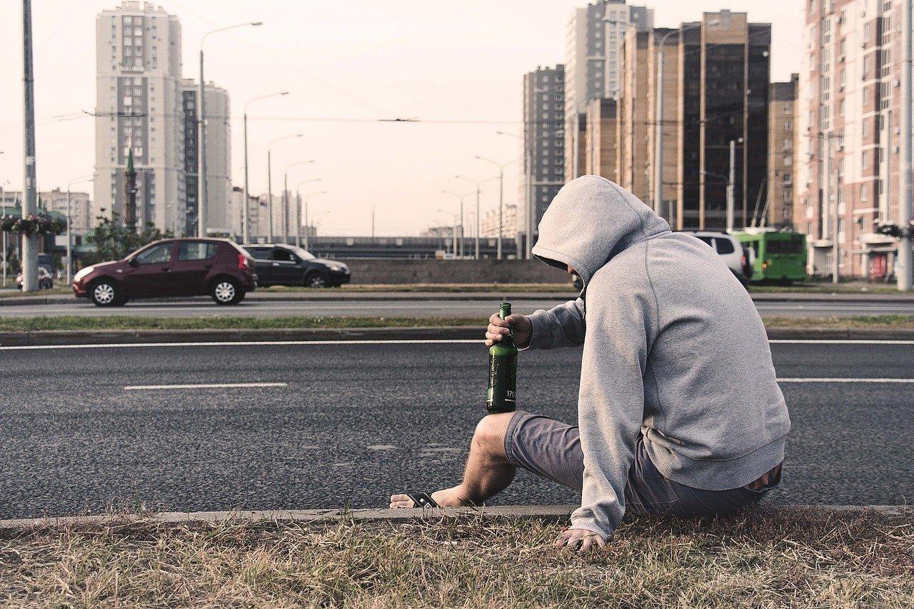 Homem com uma garrafa de bebida sentado na calçada
